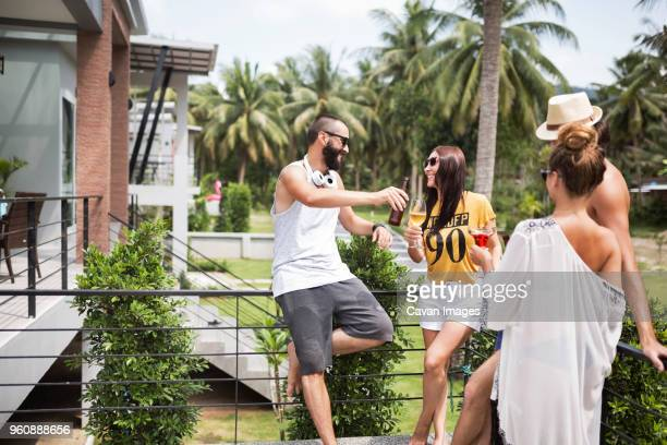 Cheerful male and female friends having drinks at tourist resort