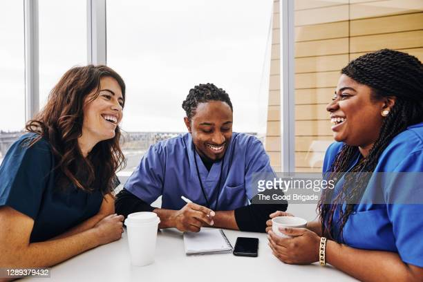 cheerful male and female nurses talking at table in hospital - diversity stock pictures, royalty-free photos & images