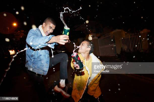 cheerful male and female splashing drink - men friends beer outside stock pictures, royalty-free photos & images