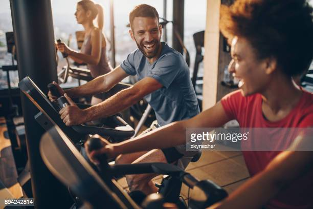 Cheerful male athlete talking to his friend on spinning training in a health club.