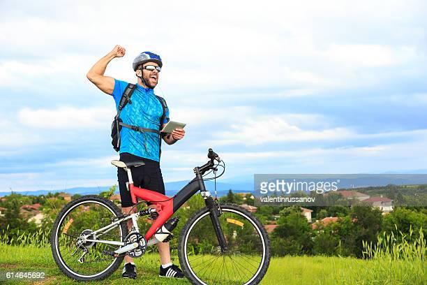 Cheerful male biker using digital tablet