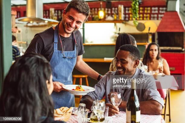 chef masculino alegre, servindo o casal no restaurante e sorrindo - satisfação - fotografias e filmes do acervo