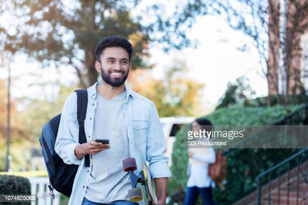 cheerful male college student carries skateboard through campus - college application stock photos and pictures