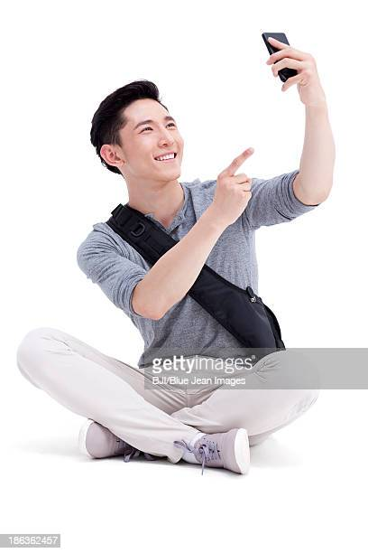 Cheerful male college student with smart phone
