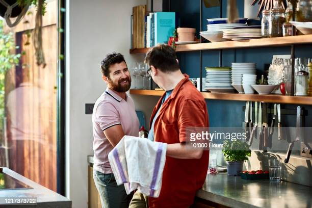cheerful male couple washing up together in kitchen - cleaning stock pictures, royalty-free photos & images