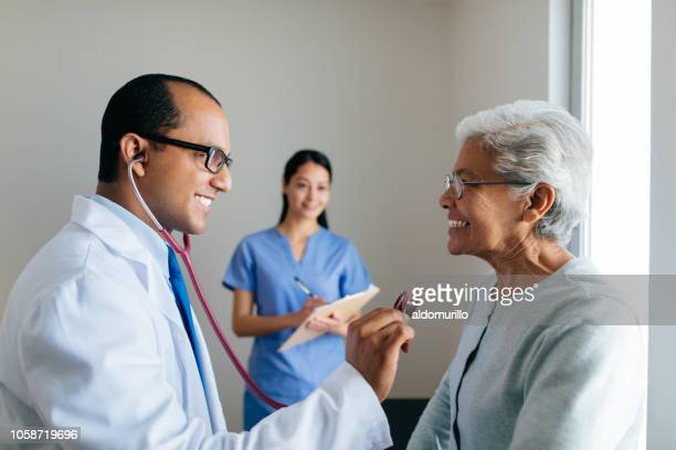 cheerful male doctor checking patient's heart and nurse in background - assistant stock pictures, royalty-free photos & images