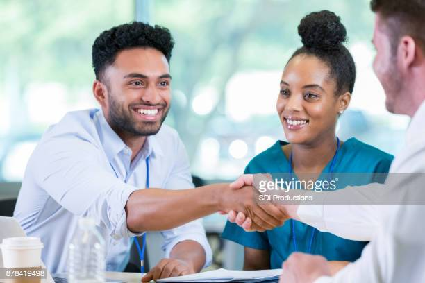 cheerful male doctor shakes a colleagues hand during meeting - administrative professionals stock pictures, royalty-free photos & images