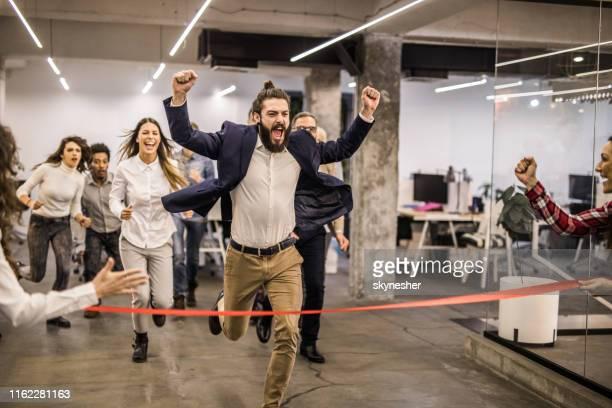 fröhliche freiberufliche männer feiern den sieg im sportrennen im casual office. - ziellinie stock-fotos und bilder
