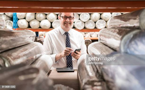 cheerful male manager in carpet factory using smartphone - camera point of view stock photos and pictures