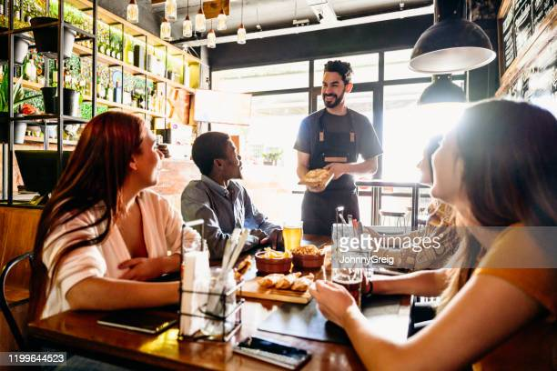 cheerful male waiter delivering empanadas to customers - empanada stock pictures, royalty-free photos & images