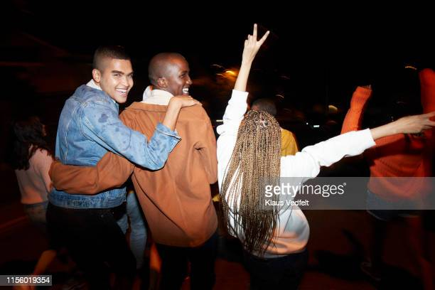 cheerful males dancing with friends at night - youth culture stock pictures, royalty-free photos & images