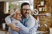 Cheerful man and his senior father embracing while greeting in the kitchen.