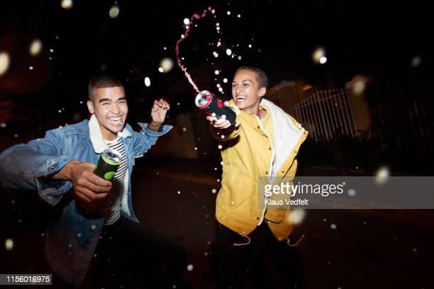 cheerful man and woman splashing drink - generation z stock-fotos und bilder