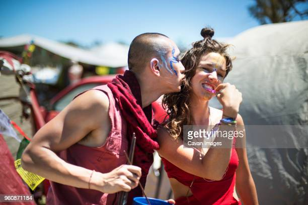 cheerful man and woman with face paints enjoying during traditional event - body paint stock pictures, royalty-free photos & images