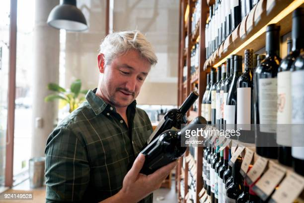 cheerful man at a wine store choosing wines and reading the labels happy - liquor store stock pictures, royalty-free photos & images