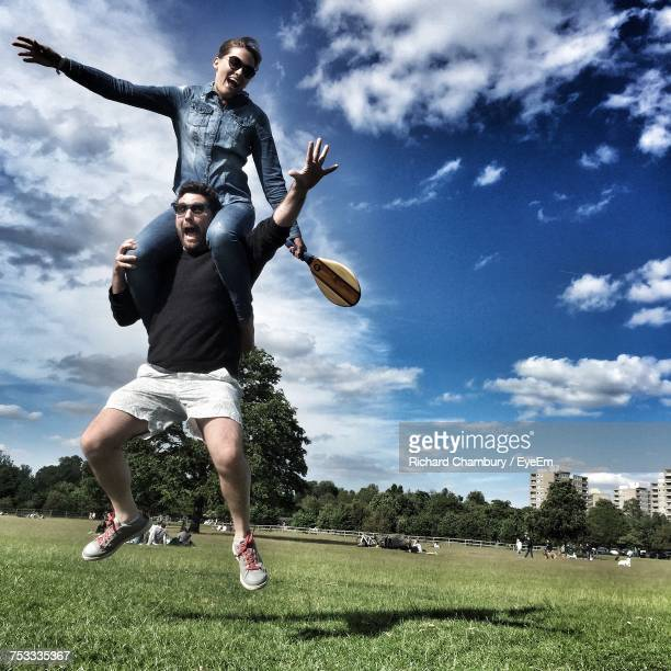 Cheerful Man Carrying Girlfriend On Shoulders While Jumping At Richmond Park