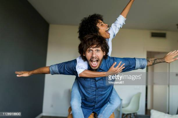 cheerful man carrying girlfriend piggyback at home - 30 39 jaar stockfoto's en -beelden