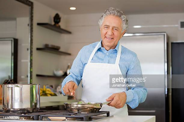 A cheerful man cooking in a domestic kitchen