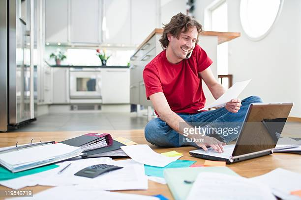 Cheerful man doing domestic paperwork on floor