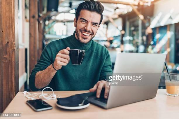homme gai buvant le café et utilisant l'ordinateur portatif dans le café - travailleur indépendant photos et images de collection