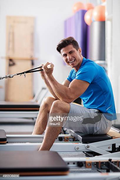 Cheerful man exercising on Pilates machine in a health club.