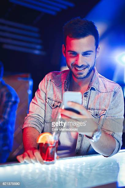 Cheerful man having cocktail while text messaging in nightclub