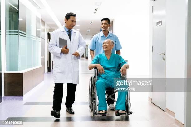車いす男性医師に向かって笑顔で陽気な男