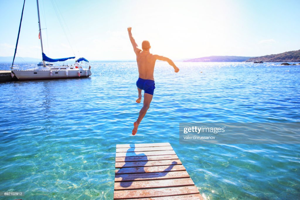 Cheerful man jumping into water : Stock Photo