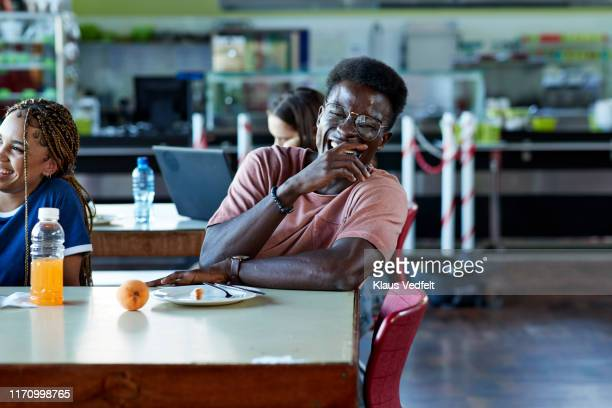 cheerful man laughing by female friend at table - africa stock pictures, royalty-free photos & images