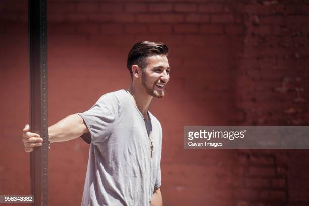 Cheerful man leaning on street sign against brick wall
