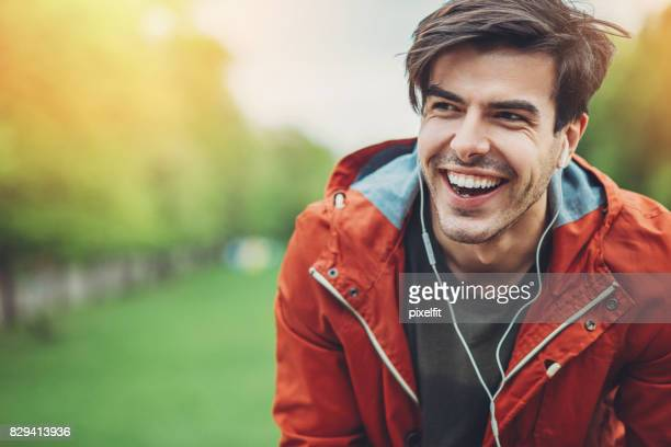 Cheerful man listening music in the park
