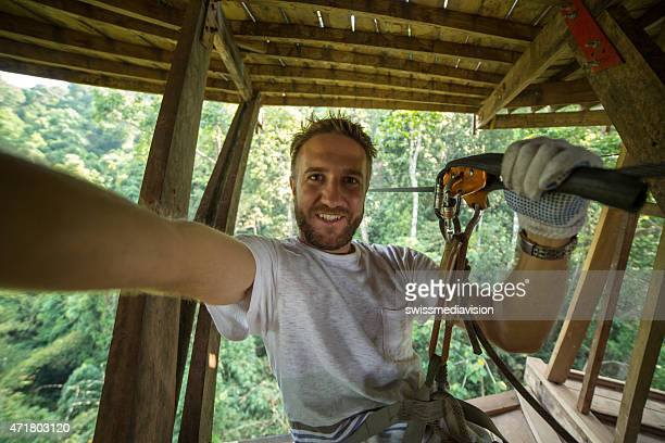 Cheerful man on canopy tour adventure taking selfie