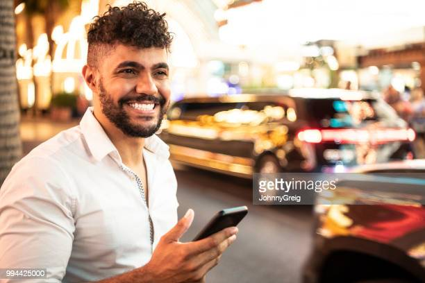 cheerful man on night out holding using app on mobile phone - fremont street las vegas stock pictures, royalty-free photos & images