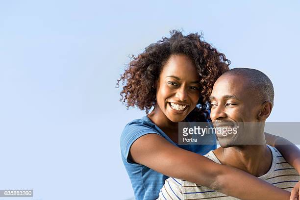 Cheerful man piggybacking woman against clear sky
