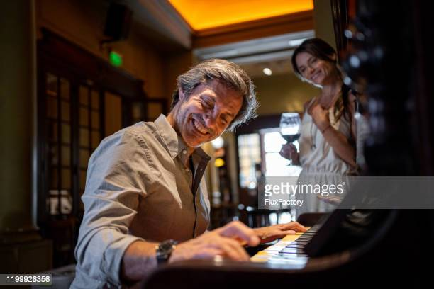 cheerful man playing a piano for his wife at a restaurant - keyboard player stock pictures, royalty-free photos & images