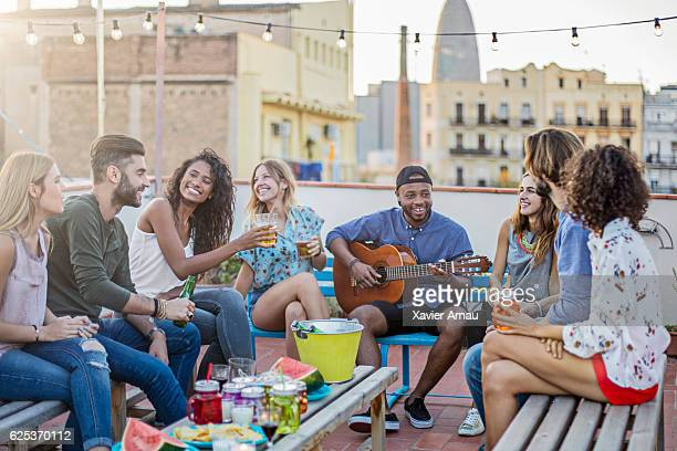 Cheerful man playing guitar for friends on terrace
