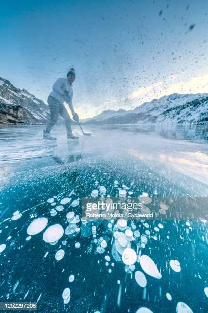 cheerful man playing ice hockey, lake sils, switzerland - schaats ijs stockfoto's en -beelden