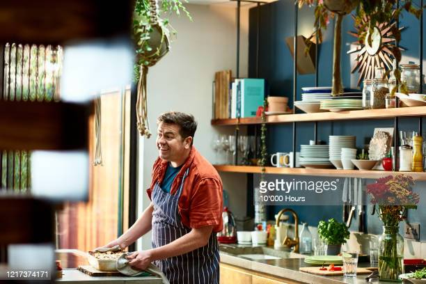 cheerful man preparing homemade in kitchen - one mid adult man only stock pictures, royalty-free photos & images