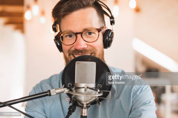 cheerful man recording a podcast from home - radio stock pictures, royalty-free photos & images