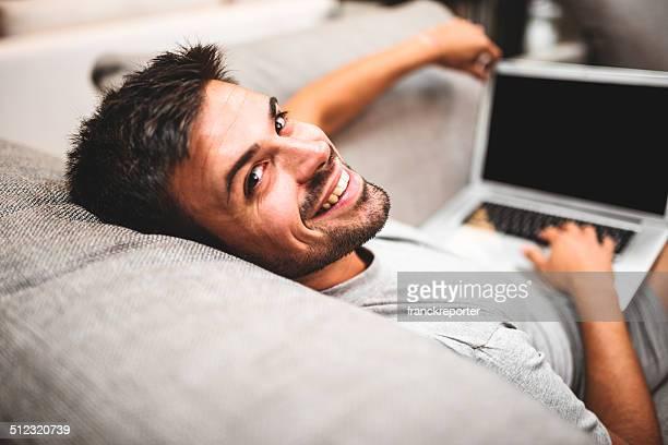 Alegre hombre relajante en sofá en línea