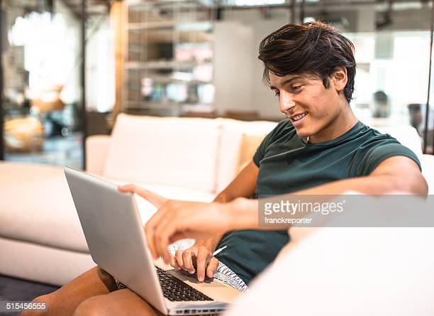 Cheerful man relaxing online on sofa