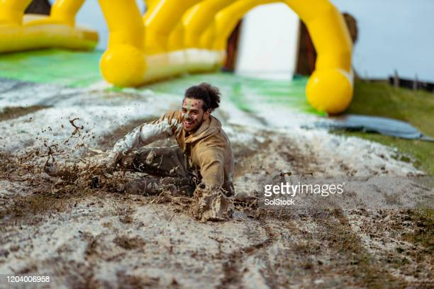 cheerful man splashing on muddy slip and slide - charity and relief work stock pictures, royalty-free photos & images