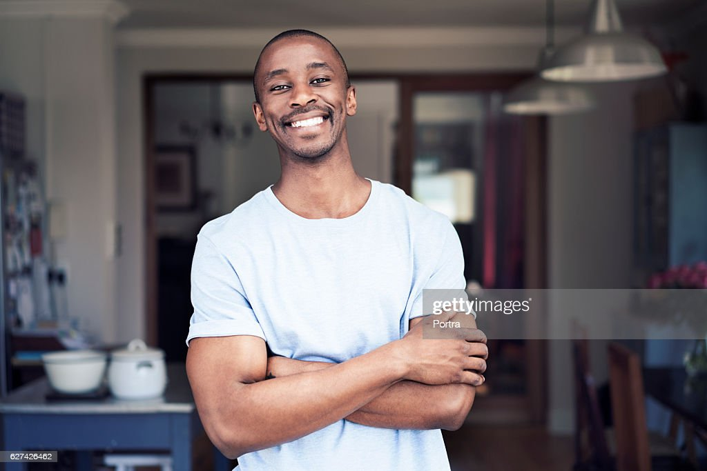 Cheerful man standing arms crossed at home : Stock Photo