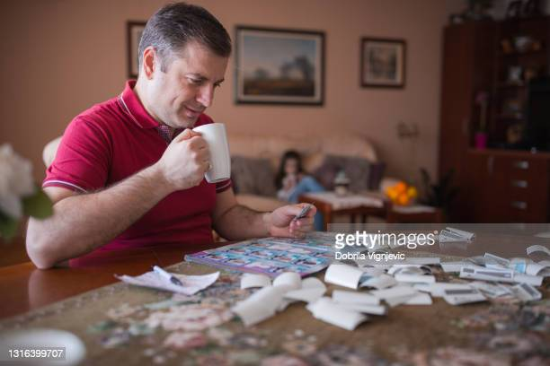 cheerful man taking a coffee break when filling in uefa 2021 sticker album at home - final game stock pictures, royalty-free photos & images
