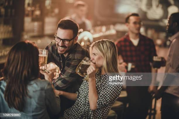 バーで彼の女友達に話す陽気な男。 - パブ ストックフォトと画像