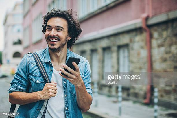 Cheerful man texting on the street