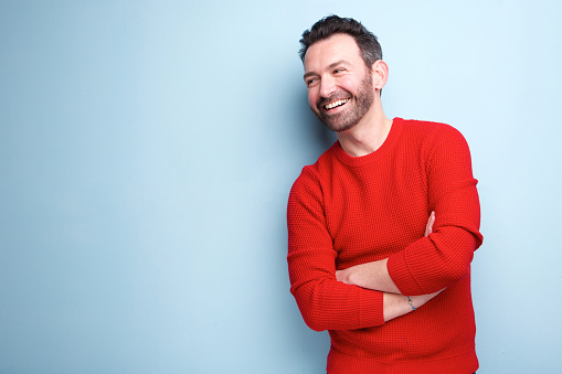 cheerful man with beard laughing against blue background 1034931492
