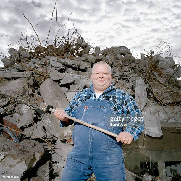 Cheerful Man with Sledgehammer at Demolition Site