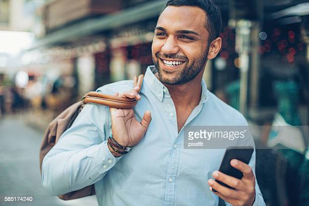 Cheerful man with smart phone outdoors