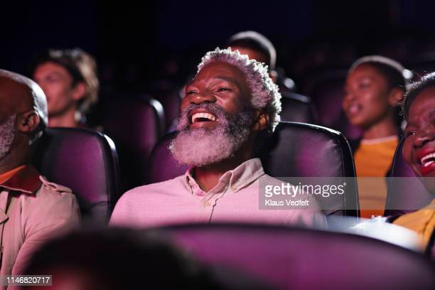 cheerful man with spectators watching movie in cinema hall at theater - comedy film stock pictures, royalty-free photos & images